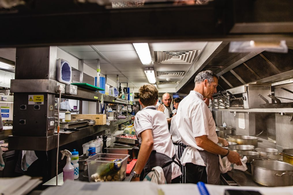 A commercial kitchen scene with the head chef (Phil Howard) cooking calmly at the stove and behind him two young chefs are reaching to each other to pass something.