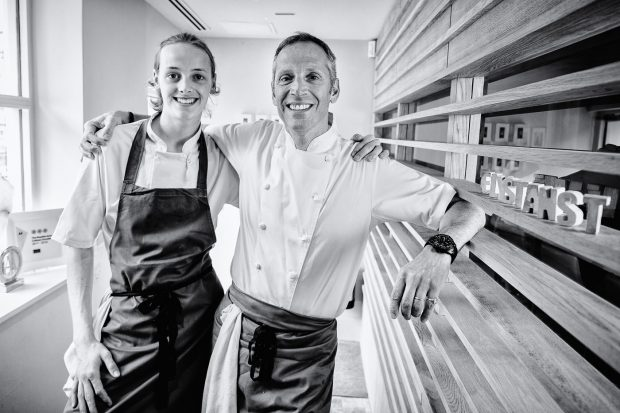 Chef Phil Howard and his son post in a black and white environmental portrait in the entrance of Elystan Street restaurant. A young and older male, in chefs attire posing with their arms around each others shoulders, smiling to camera