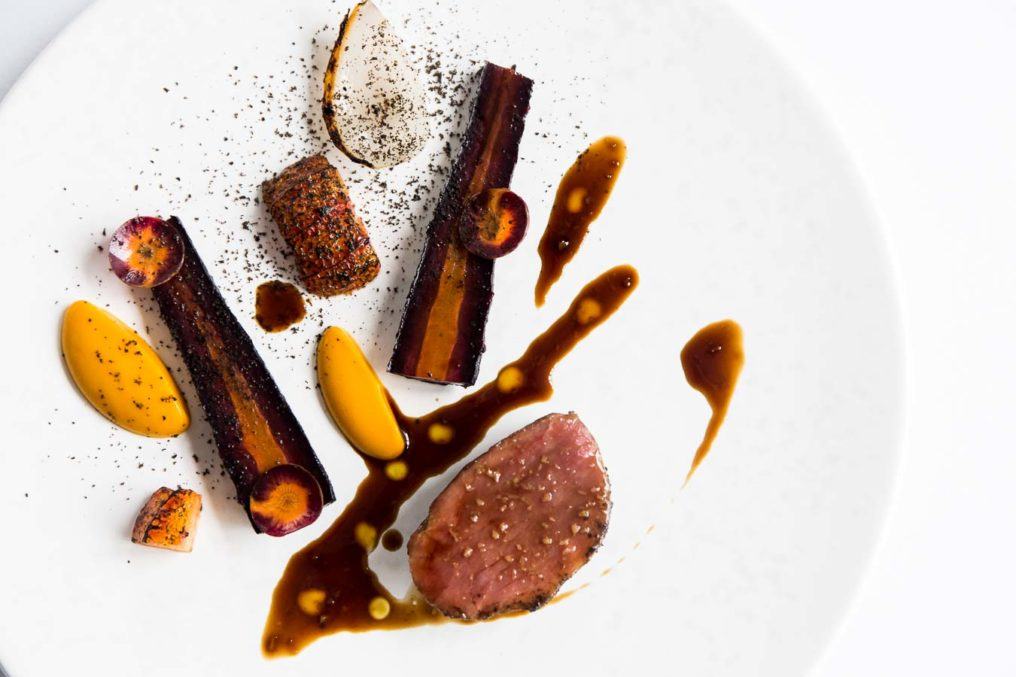 Top down photo of a piece of cooked Iberian pork, carrots, purées and sauce on a white plate, served fine dining at The Ledbury by Brett Graham