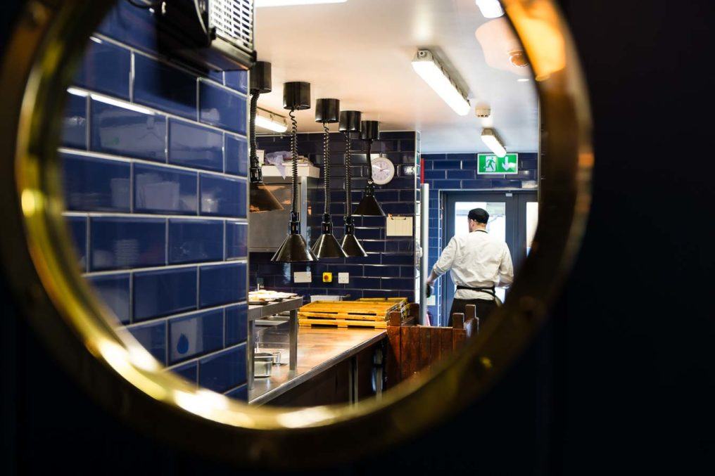 View of a commercial kitchen with blue subway tiles, looking through a round window with a brass surround, where you can see a chef walking through the kitchen