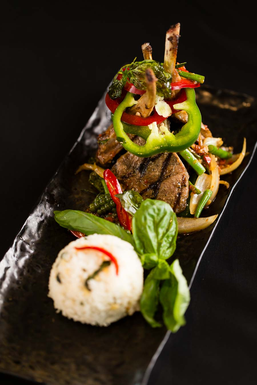 A textured, dark, rectangular plate with meat on the bone, bell peppers, herbs and a ball of white rice, on a black background