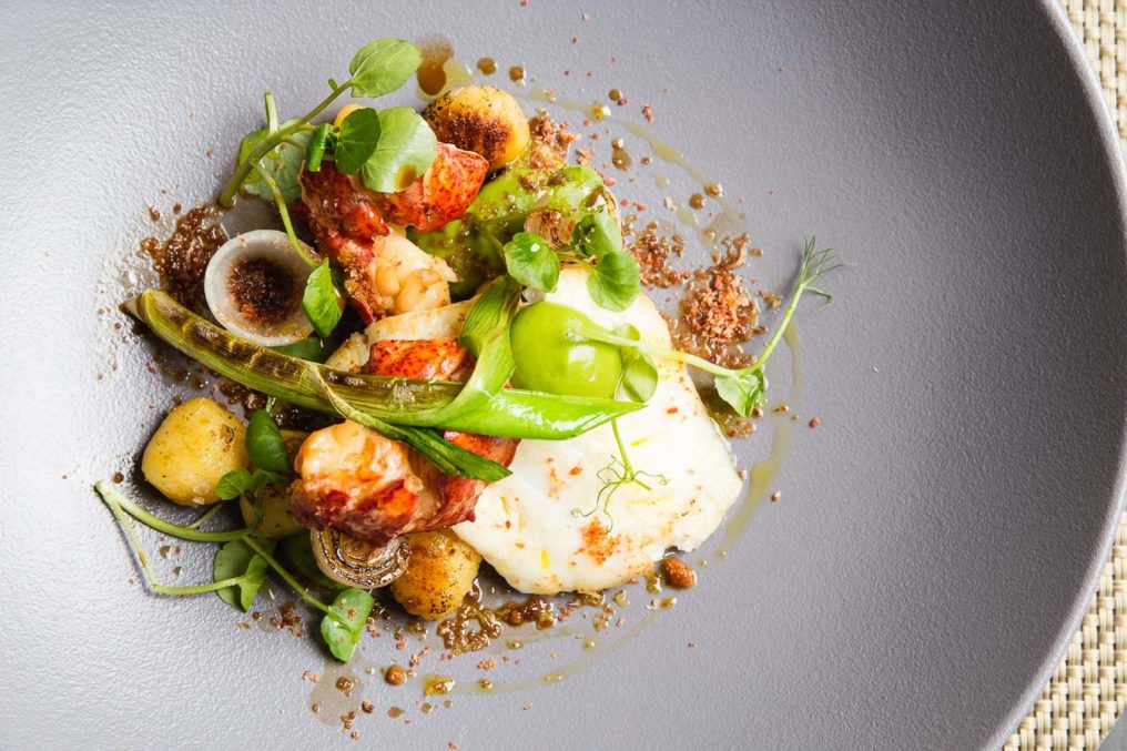Fine dining style langoustines with onion, pea purée, mini leek and pea sprouts on a grey textured plate