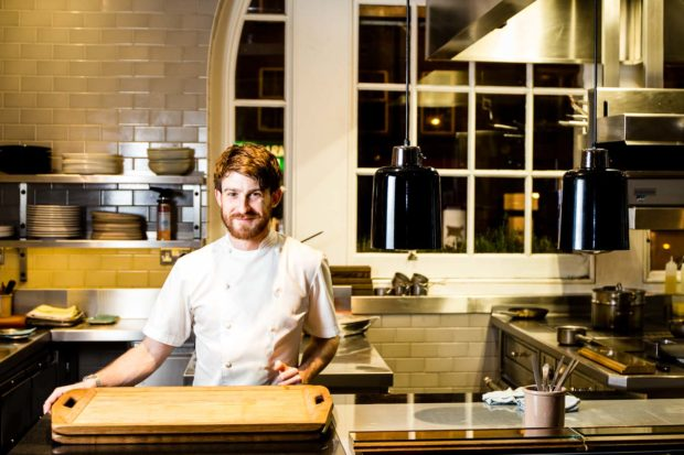 Environmental portrait of chef Lee Westcott at the pass of his kitchen at Typing Room, Bethnal Green, London. Young bearded male in chefs whites stands behind the serving pass of a fine dining restaurant. A night street scene can be seen through the window