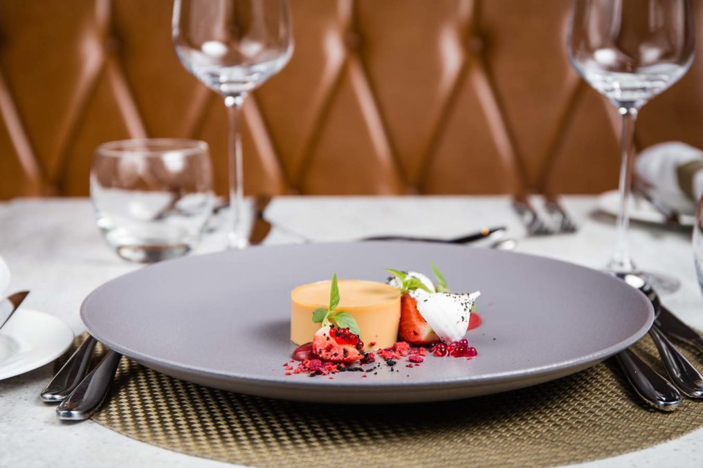 Fine dining styled lemon, strawberry, meringue dessert with the table place settings