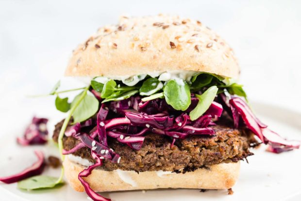 A front shot of a lentil veggie burger in a rustic seeded bun with shredded red cabbage, baby spinach and a white dressing