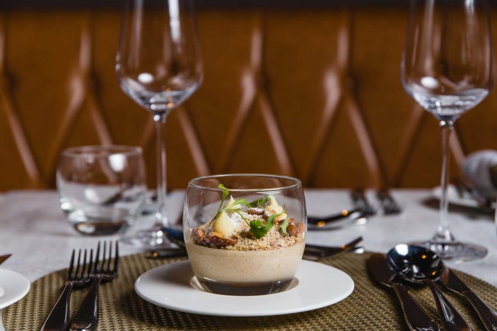 A creamy dessert with a crumbled topping served in a glass tumbler, in a fine dining table layout