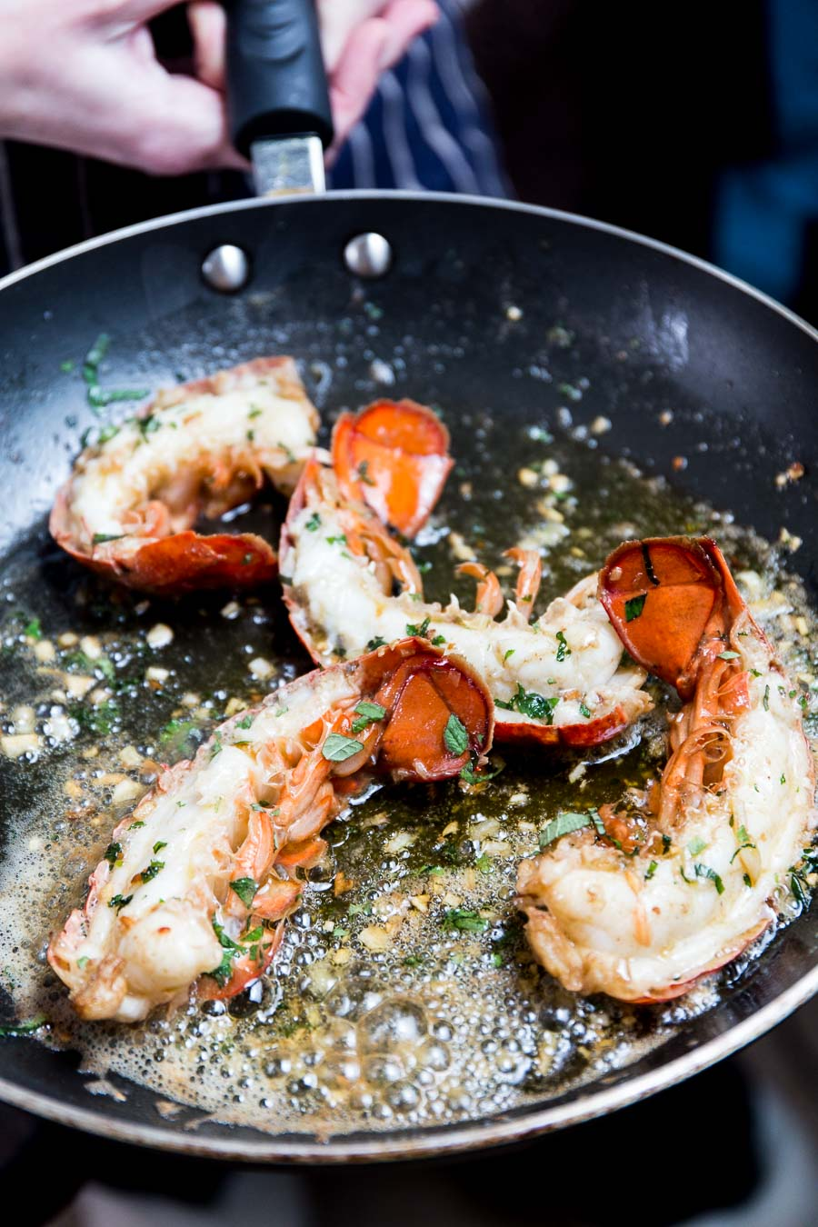 A close shot of someone holding a frying pan containing cooked lobster tails with bubbling garlic butter and green herbs