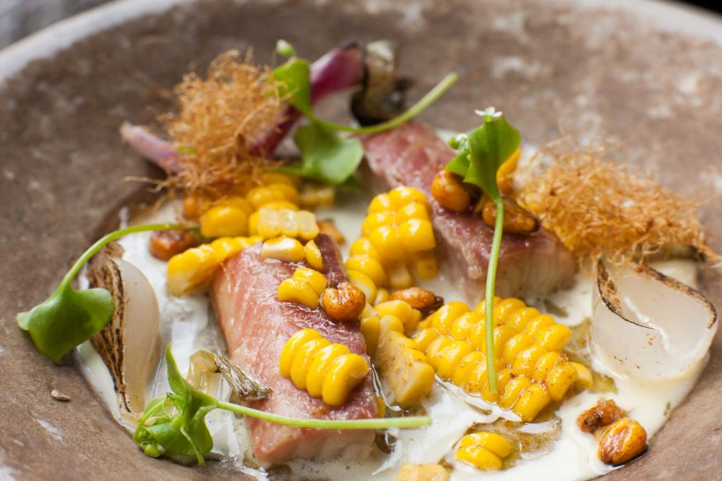 Bistro style mackerel in white space with sweetcorn, clams in a light brown, textured stone bowl, from The Dairy by Robin Gill