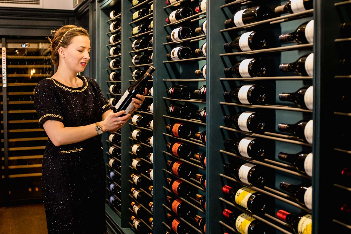 Lady in black and gold dress reading the wine label with a large wine rack along the whole wall in front of her. Margriet Crump, Sommelier