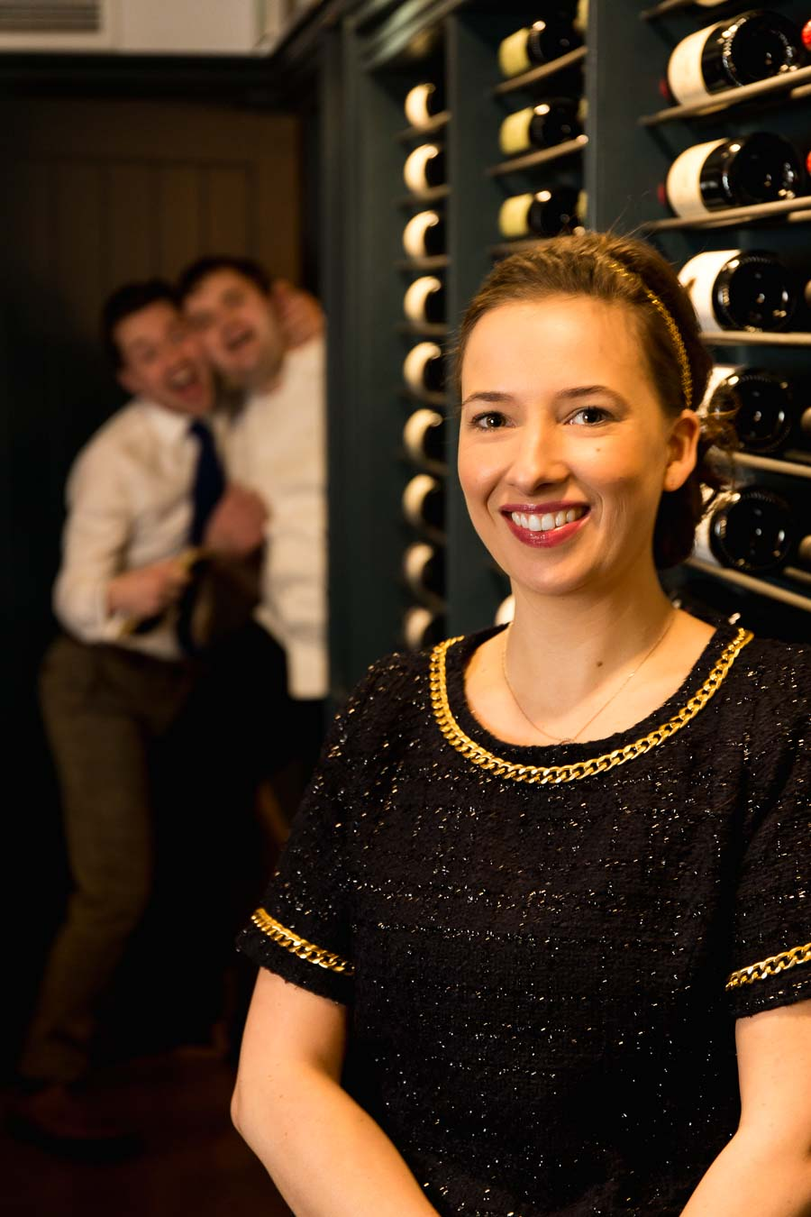 Portrait of Margriet Crump, Sommelier in the wine attic of The Oxford Blue Pub whilst Steven Ellis and Dan Crump joke around photo bombing in the background