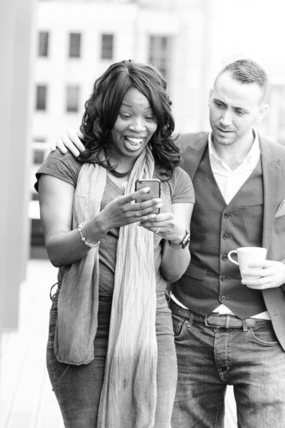 A black female wearing casual clothes look excitedly at her phone she is holding while a caucasian man wearing semi formal clothes looks over her shoulder with his hand on her opposite shoulder, as he carried a coffee mug. Background is a soft urban scene