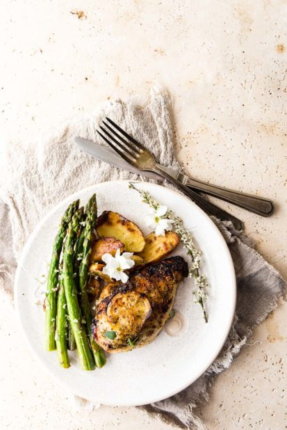 Flat lay of lemon roasted chicken on a white textured plate accompanied by roasted potatoes and asparagus, on a stone table top and textured cloth