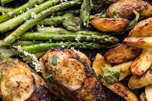 Top down photo of roasted lemon chicken breast with asparagus and roast potatoes garnished with small white wild flowers