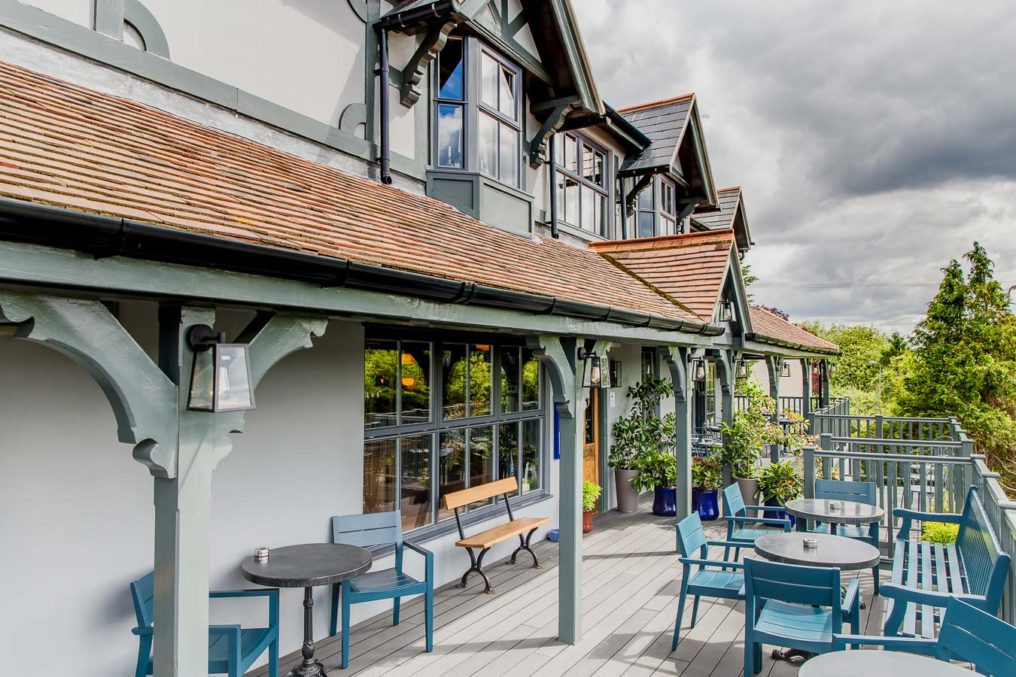 External photo of a gastropub front patio, with tables and chairs, potted plants, trees, in bright sunlight with a dramatic cloudy sky. The Oxford Blue Pub, Windsor
