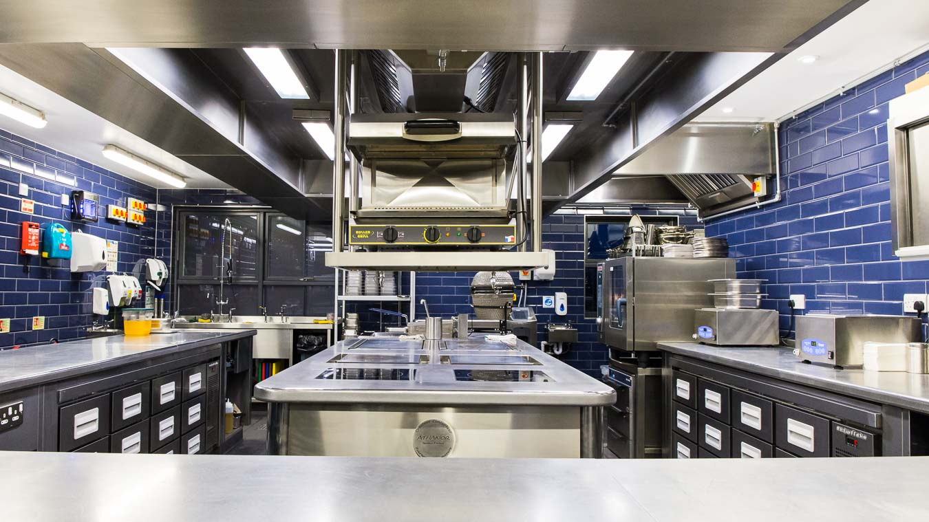 Pristinely clean commercial kitchen with stainless steel surfaces and blue tiles. Kitchen of The Oxford Blue gastropub