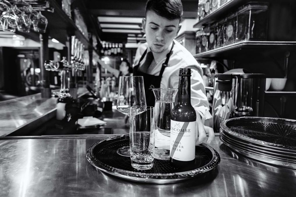 Bartender serving drink at The Oxford Blue Pub. Young male leans towards camera to pick up the drinks tray
