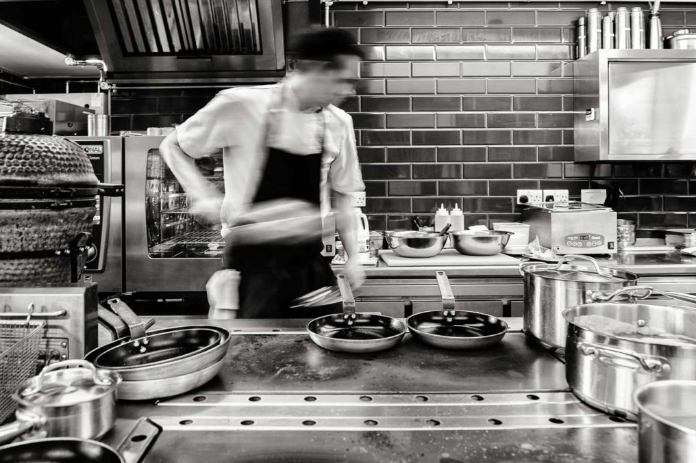 Black and white image of a chef at the stove, moving to the right with motion blur