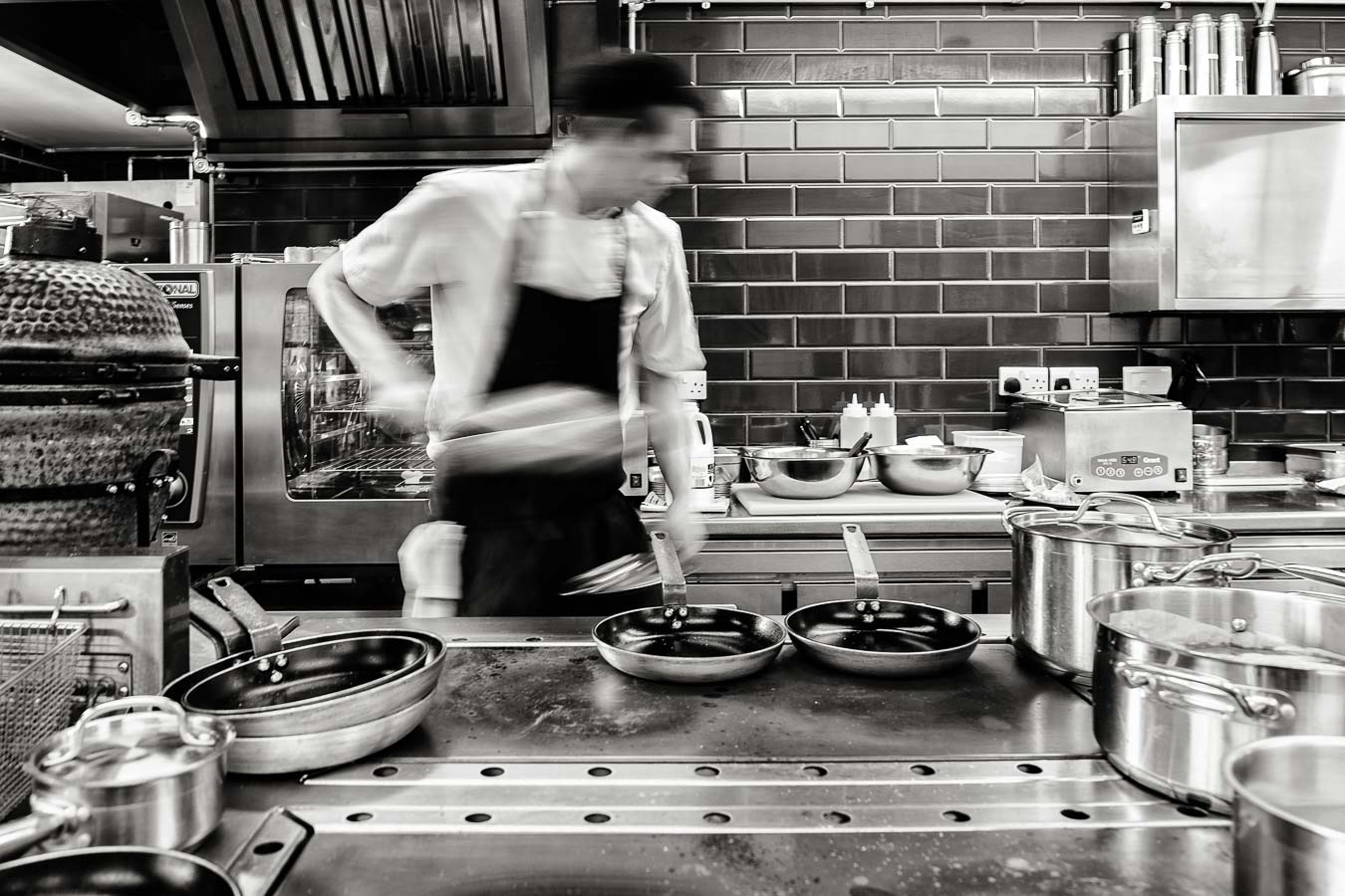 A chef at the stove, holding a pan and moving to the right causing motion blur