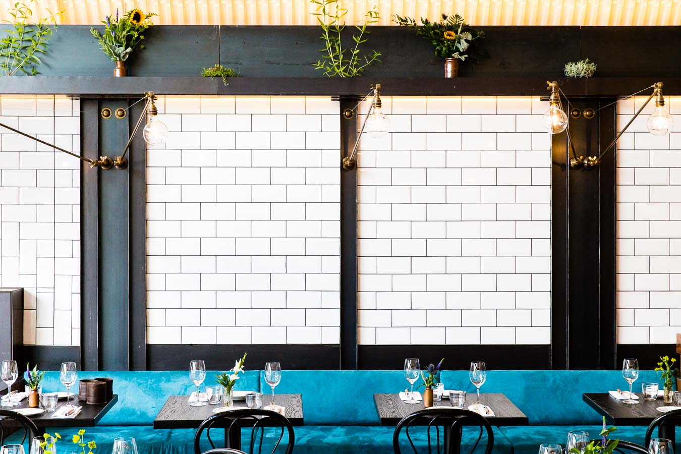 White tiled wall of a restaurant with dark ironwork pillars, blue brushed cotton seating, industrial style lights and potted plants. Paradise Garage by Robin Gill