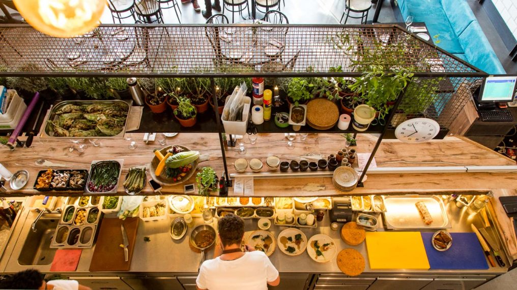 Looking down at the open kitchen of Paradise Garage restaurant, with prepped food in containers, a chef plating up the food, fresh potted herbs