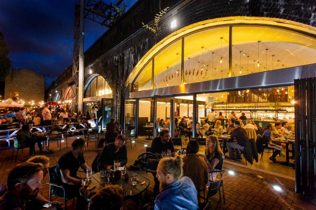 Night time external photo of diners outside on a patio and inside an open fronted restaurant with a glass , arched front. Lights glow from inside and adjacent bars can be seen in the background