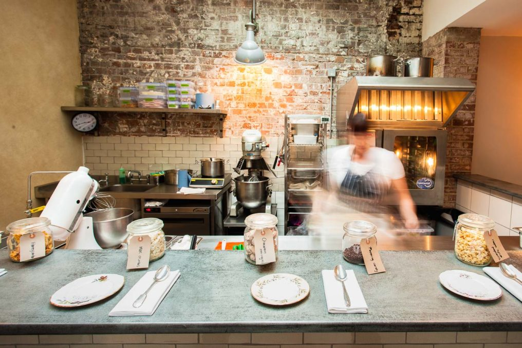 A chef is working behind the dessert bar with motion blur. Jars of candy are lined up on the bar with small serving plate. Commercial ovens and mixer can be seen in the background along with a rustic brick wall.