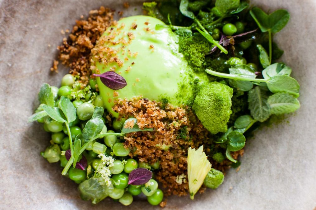 A stone dish with a round greenmail of pea mousse, with a crumb, peas, pea chutes and small mint leaves