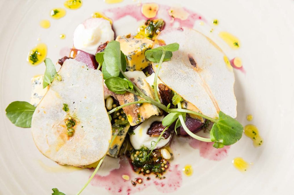 Top down, fine dining dish with thin slices of pear, pea chutes, blue cheese and beetroot, circled by yellow drops of infused oil