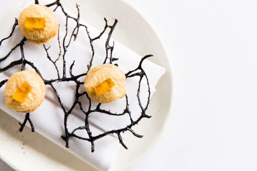 Small round pastries with rectangles of orange jelly on top sitting on dried seaweed