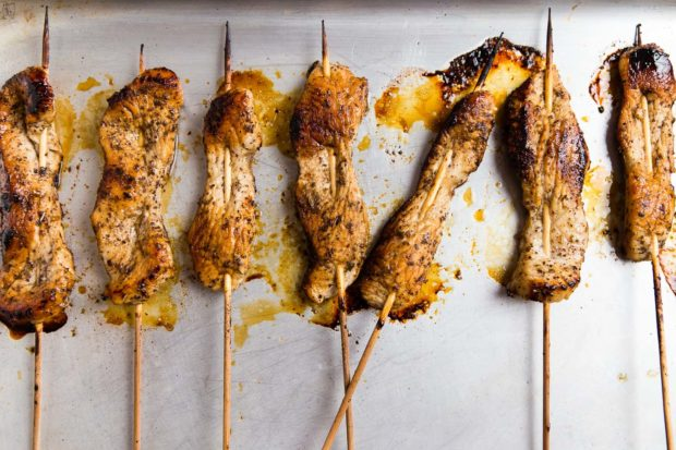 Wooden skewers through chicken pieces laying on a sliver baking tray with cooking juices