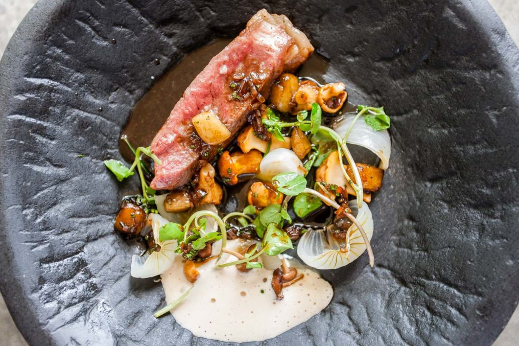 Top down photo of a dark grey, stone dish with random ridges. In the dish is a rectangle piece of cooked pork sitting next to small mushrooms, peas chutes, white onions with a white sauce and gravy