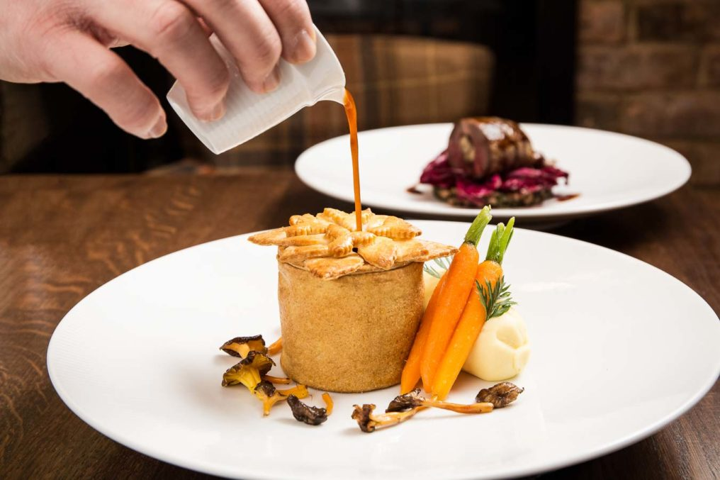 Gravy being poured into the top of a gastro pub pie. Food is on a white plate with turned carrots, mash potato and mushrooms. In the background is a different dish and a tweed chair