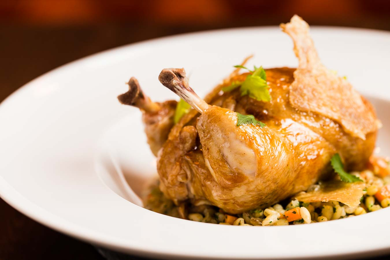 A golden, roasted poussin sitting on a bed of wild rice, all in a white, wide rimmed bowl