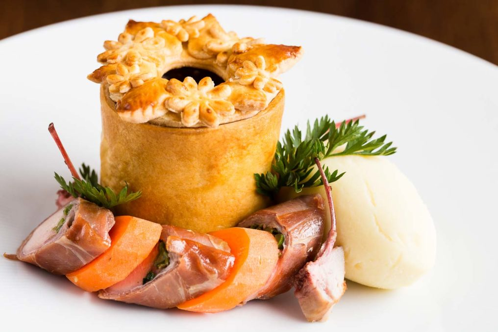 A pastry pie with an ornate pastry lid sits on a white plate surrounded by disc slices of meat and carrot alternating with a small rib meat and a large quenelle of mash potato