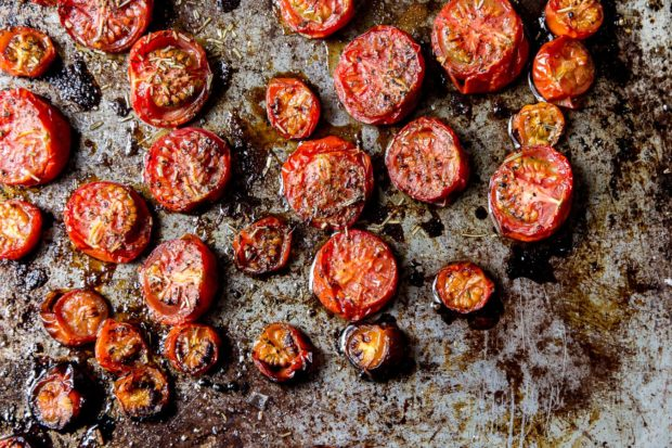 A rustic baking tray with roasted tomato halves and all the juices