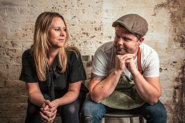 Fun portrait of Sarah and Robin Gill sitting side by side looking at each other with a rustic brick wall background