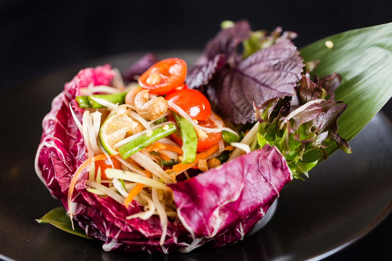 A dramatic photo of a Thai salad of cashews, tomato, green beans, sliced cabbage nestled in a large red cabbage leaf which sits on a black plate