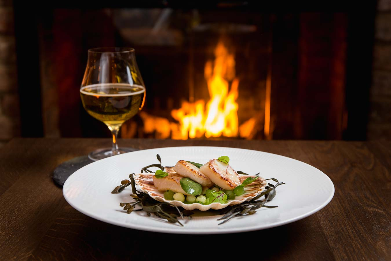 A gastro pub scene of a scollops dish with green herbs, in a large shell, on a bed of seaweed. accompanied by a glass of wine and a roaring fire in the background