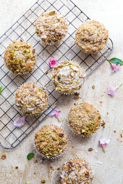 Flat lay of muffins topped with nuts on a textured background with a cooling rack and edible flowers