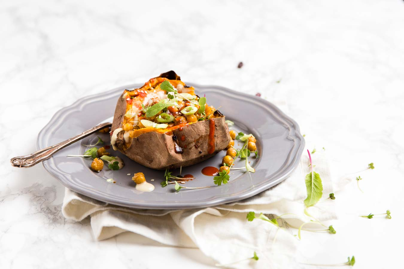 A sliced open baked sweet potato with a chick pea and spring onion tomato topping, on a grey plate with green micro herbs, a white linen textile and white marble table top