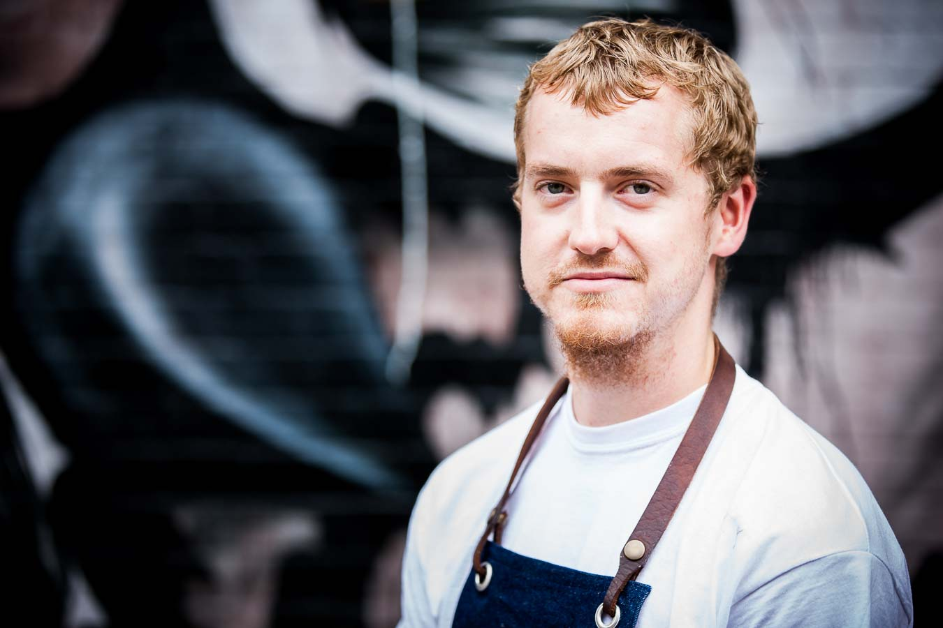 Environmental portrait of chef Simon Woodrow, wearing a white t-shirt and denim apron, with a graffiti wall, out of focus, behind him