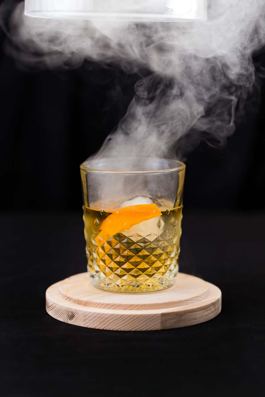 A crystal tumbler containing an amber drink, ice cub and orange wedge sits on a light, wooden base with a smoke plume rising from the glass as glass cover is being lifted from over the top, with a black surround and background