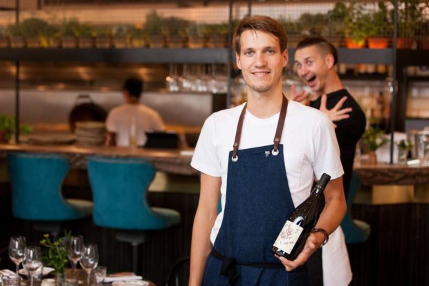 Environmental portrait of the Sommelier at Paradise Garage standing holding a bottle of wine while his colleague photobombs with a smile and jazz hands