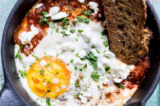 Top down shot of a black cast iron skillet containing a baked egg with a spicy tomato sauce, chopped green herbs and a slice of artisan bread