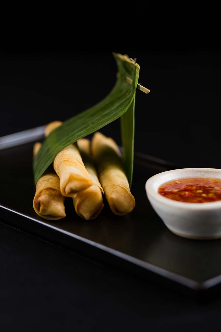 Dramatic shot of Thai spring rolls wrapped in a leaf on a black plate with a small bowl of red dipping sauce next to them.