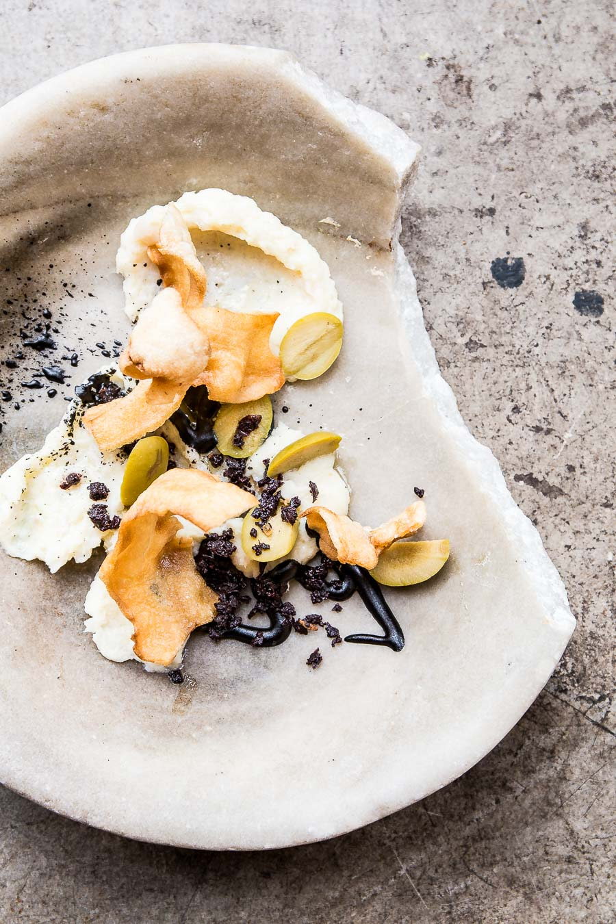 Dark coloured squid ink, prawn crackers and sliced olive sit on a partially broken, thick, stone bowl with restaurant styling and a stone floor tile as the background