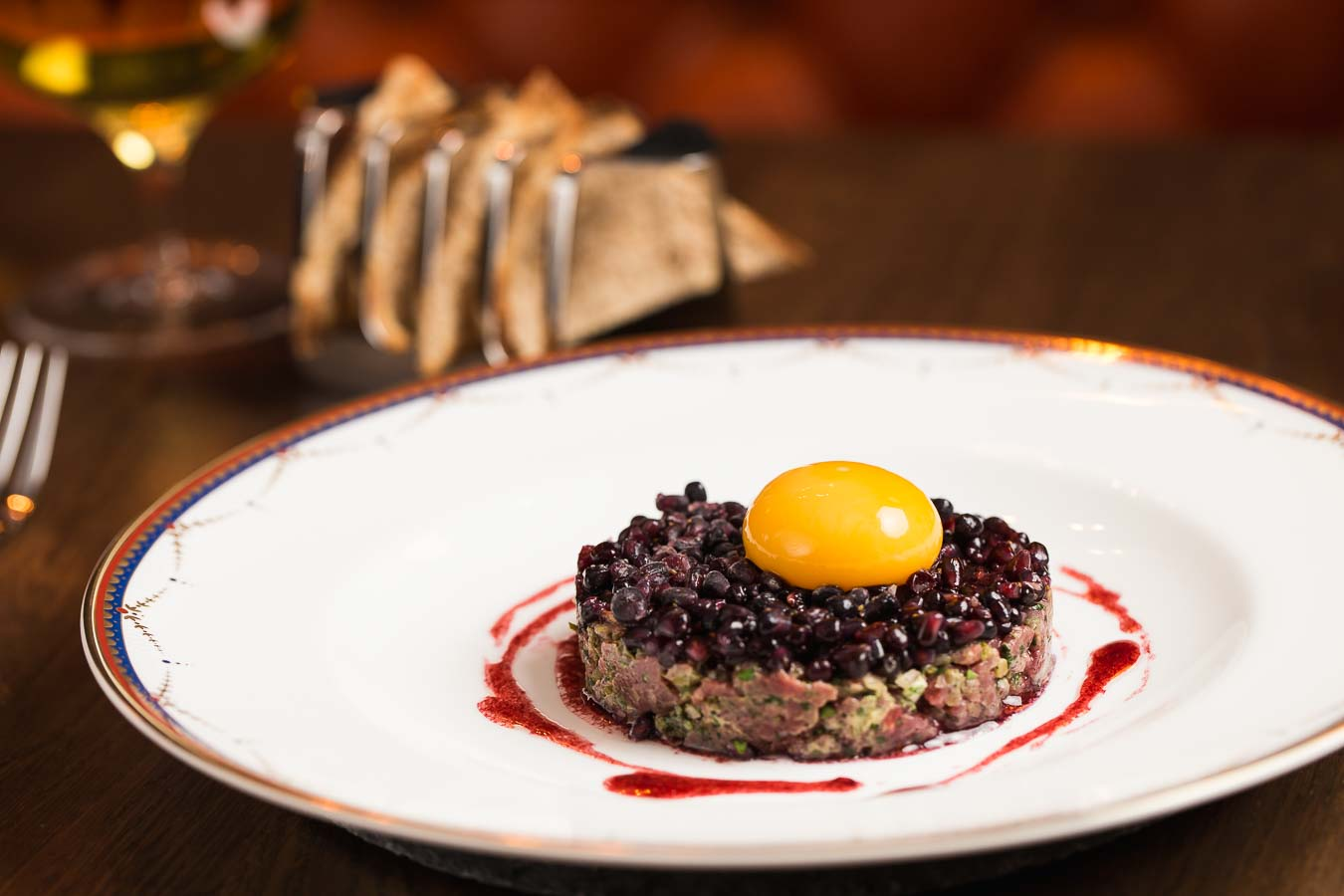 Gastro Pub style steak tartare, formed in a circle, topped with blackcurrants and the yoke of a hens egg on top. In the background is a wine glass and artisan toast crackers in a toast rack