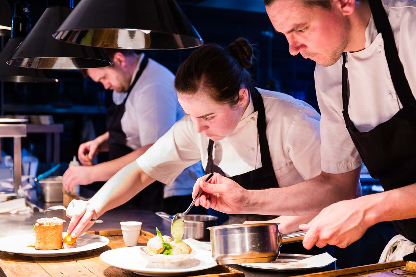 Three chefs looking very focused, plating up food on the pass of The Oxford Blue Pub, with Ami Blakey and Steven Ellis