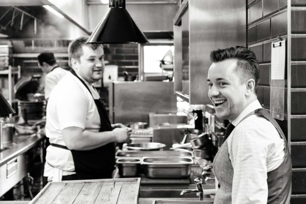 Candid fun photo in the kitchen of The Oxford Blue Pub, during service prep with Daniel Crump turning towards camera with a big smile and Chef Steven Ellis joining in from his prep station in the background