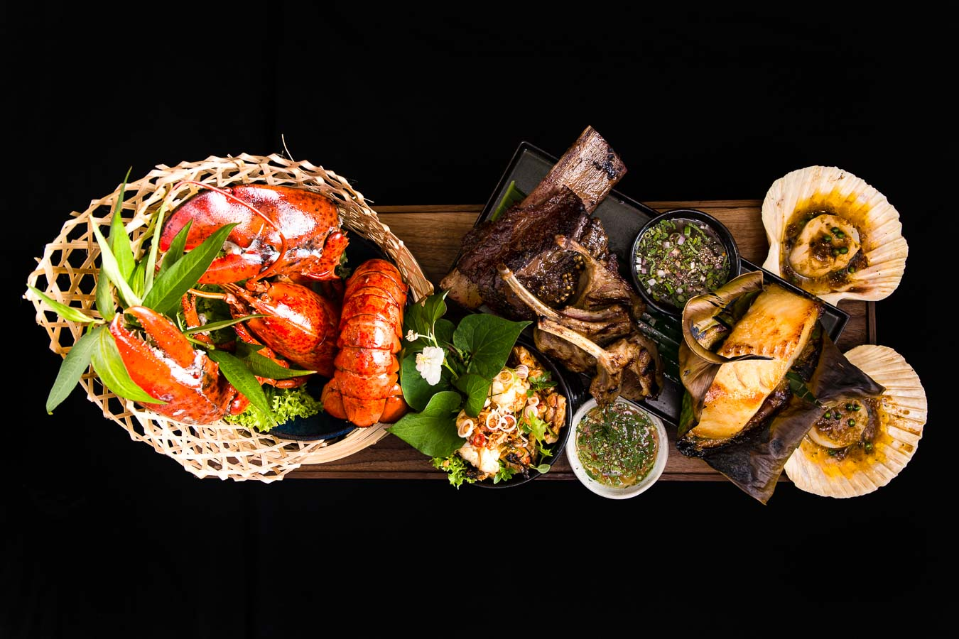 Top down, dramatic photo of a sharing seafood platter. Including a wicker basket of cooked lobster tails and claws, ribs, fish, dipping sauces and oysters in their shells. A celebration of surf and turf
